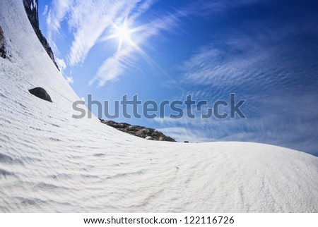 blue sky  and sunshine over snowy hills in Norway - stock photo