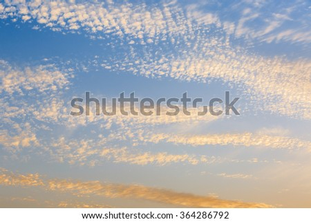 Blue sky and yellow clouds at dusk - stock photo