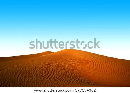 Blue sky and yellow dunes in desert - stock photo
