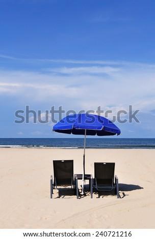 Blue sky at the beach, beach chairs and blue umbrella - stock photo