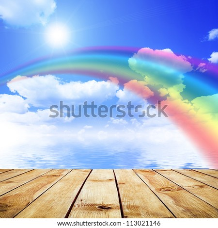 Blue sky background with rainbow and reflection in water. Wood pier - stock photo
