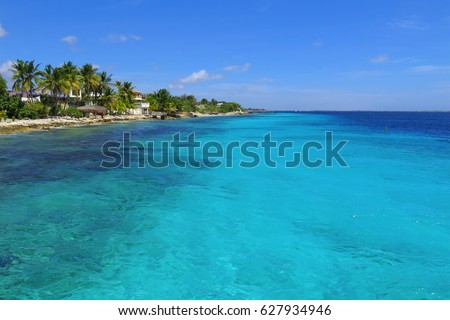 Blue sky, beautiful tropical azure sea water and coastline with green vegetation, palm trees and small romantic buildings.
