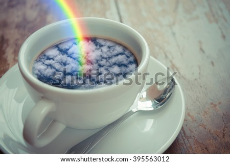 Blue sky cloud with rainbow reflection on Coffee in white cup on wood table , process in vintage style - stock photo