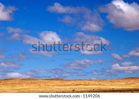 blue sky, clouds, and brown hills - stock photo