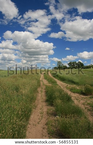 Blue sky, clouds, green grass/field with road and fence leading into the distance; Saskatchewan; Canadian prairie; summertime - stock photo