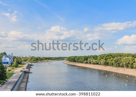 Blue sky, clouds, river water, green trees, beach, boats in spring or summer season landscape - stock photo