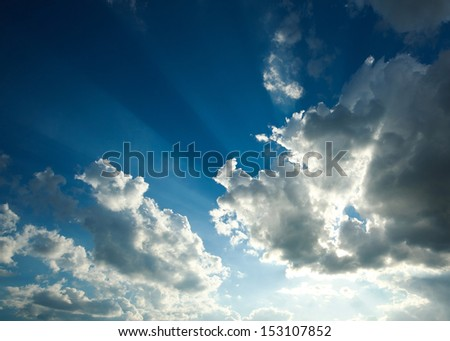 Blue sky in beams sunshine through the clouds - stock photo