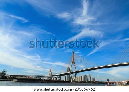 Blue sky over a bridge across the river. - stock photo