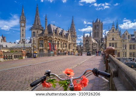Blue sky over Gent, Belgium, with a traditionally decorated bicycle in the foreground - stock photo