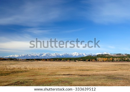 blue sky over the vast  steppes, Tunka valley, mountains covered with snow, Sayan mountains.  Used toning of the photo