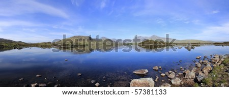 blue sky reflecting in the still water of lakes on rannoch moor in the scottish highlands - stock photo