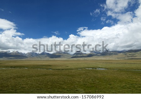 Blue sky snow-capped mountains - stock photo