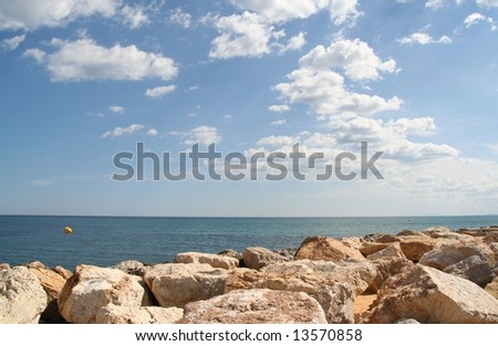 Blue sky with clouds above blue sea and stones in the foreground. - stock photo
