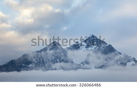 Blue sky with clouds and the Austrian Alps during sunrise.