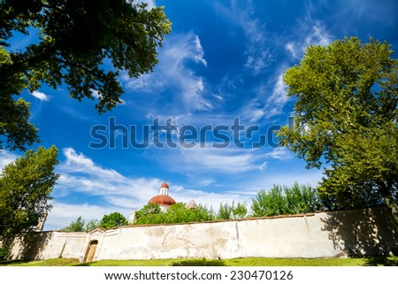 Blue sky with clouds framed by green trees old brick fence and church tower - stock photo