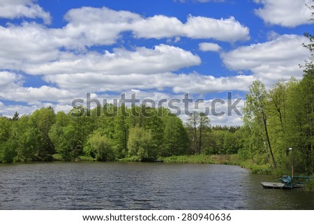 Blue sky with clouds, lake and forest at sunny day - stock photo