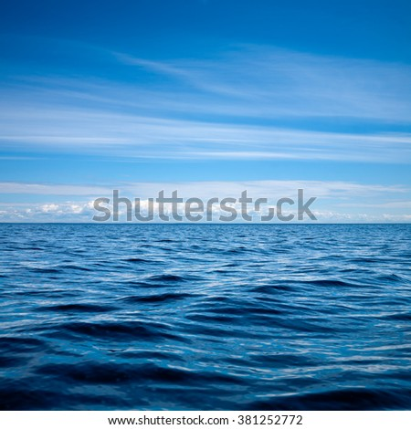 Blue sky with clouds  over a rippled lake natural background