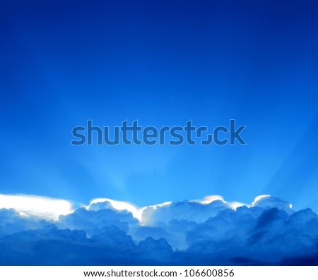 Blue sky with dramatic sunbeams and clouds - stock photo