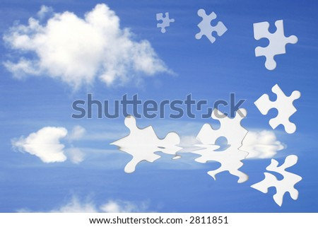 Blue sky with fluffy clouds and jigsaw pieces emerging from water