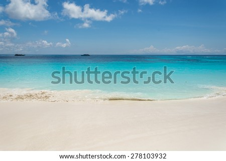 blue sky with sea and beach - soft focus with film filter
