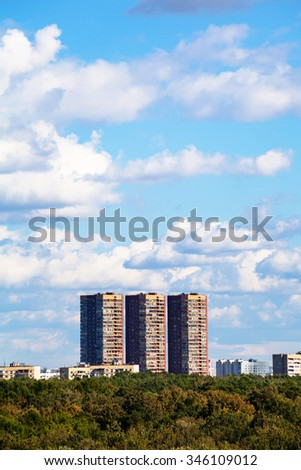 blue sky with white clouds over apartment buildings in summer