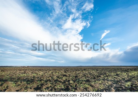 blue sky with white clouds over ploughed fileld in early spring - stock photo