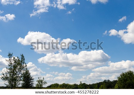 Blue sky with white clouds over the field - stock photo