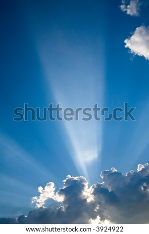 Blue skys and dramatic sunbeams bursting through the haze for a dramatic look - stock photo