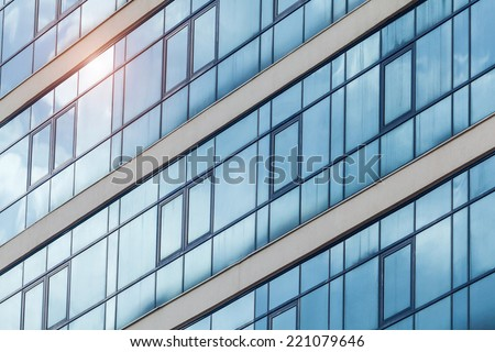 Blue skyscraper facade. In a window the sun is reflected. - stock photo