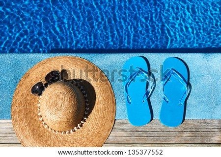 Blue slippers and hat by a swimming pool - stock photo