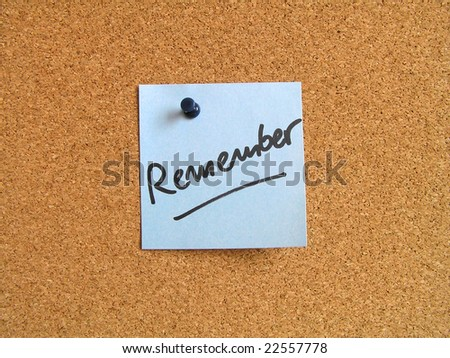 Blue small sticky note on an office cork bulletin board. Remember message. - stock photo