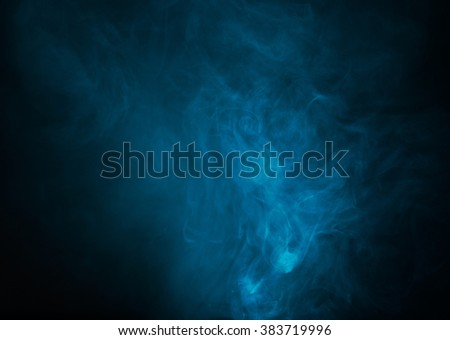 Blue smoke over black studio background