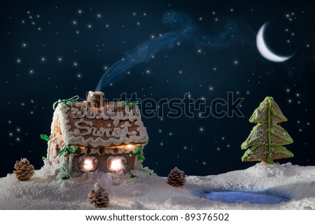 Blue smoke poured out of the gingerbread home at night in winter - stock photo