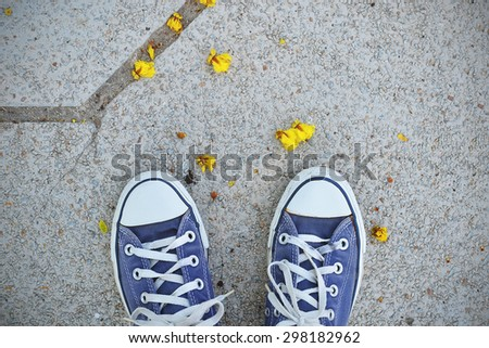 Blue Sneaker shoes standing on street. Canvas shoes on street. Top view. - stock photo
