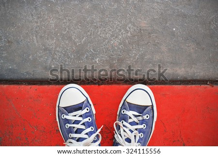 Blue Sneaker shoes standing on the red line. Canvas shoes on street. Top view. - stock photo