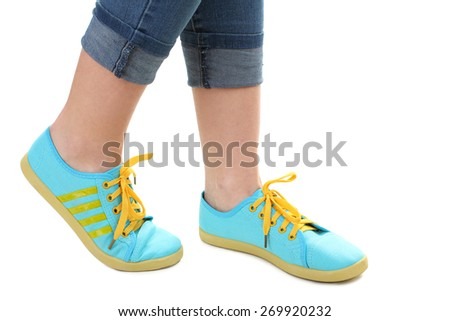 Blue sneakers on girl, young woman legs, isolated - stock photo