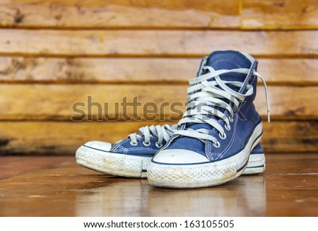 Blue sneakers on the wooden floor