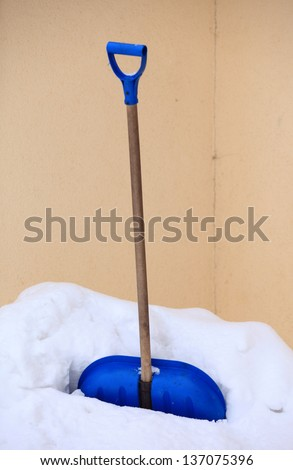 blue snow shovel standing up in deep snow, winter scenery - stock photo