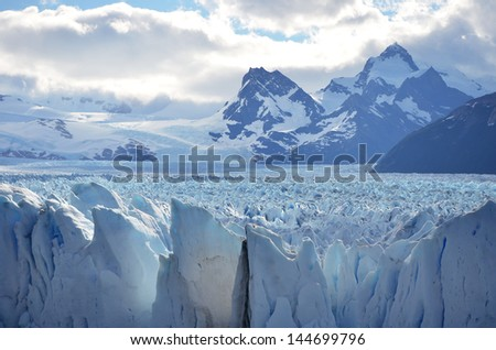 Blue snow valley of Perito Moreno glacier with mountains on the background