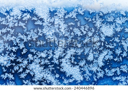 blue snowflakes and frost pattern on window in cold winter evening - stock photo