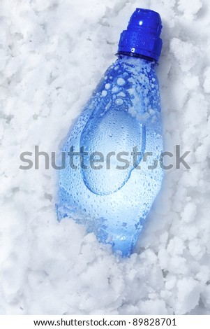 Blue soda bottle in crushed ice with back light - stock photo