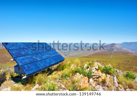 Blue solar cells against awesome mountain landscape. Shot in Salmonsdam Nature Reserve, near Hermanus and Stanford, Western Cape, South Africa.  - stock photo