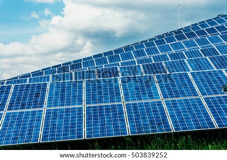 Blue solar energy panels in grid on sunny day with blue skies.