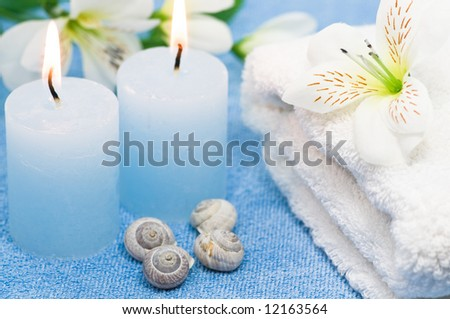 Blue spa candles with seashells, towel and decoration flowers - stock photo