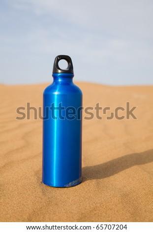 Blue sport water bottle in desert - stock photo
