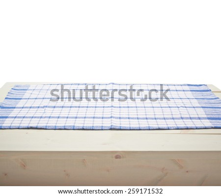 Blue squared tablecloth or towel over the surface of a wooden table, composition isolated against the white background - stock photo