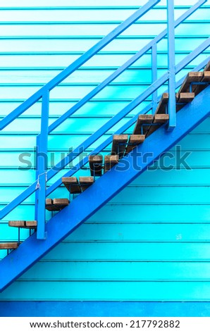 blue stairs up, wooden with blue wooden wall - stock photo