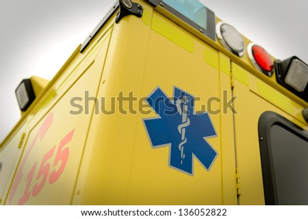 Blue star paramedic symbol and phone number on emergency truck - stock photo