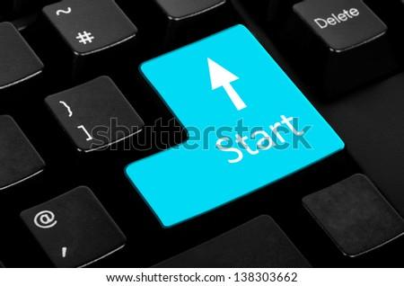 Blue start button on the black keyboard. - stock photo