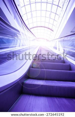blue steps of escalator in office center interior at sunny day - stock photo